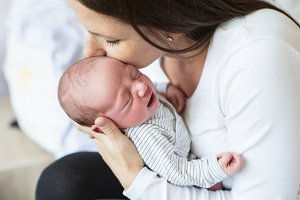 Beautiful young mother with her newborn baby son, bedroom
