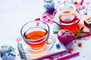 Teapot and glass cup backlight vibrant close-up. Confetti and macarons on a light background. Tea party colorful concept with copy space.