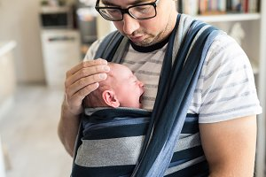 Close up of young father with his son in sling