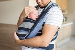 Unrecognizable young father with his son in sling