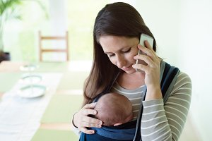 Beautiful mother with her son in sling and smartphone