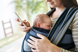 Unrecognizable mother with her son in sling and smartphone