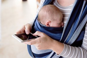 Unrecognizable mother with her son in sling, holding smartphone