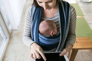 Young mother with her son in sling, holding tablet