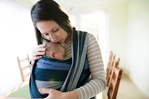 Beautiful young mother with her son in sling at home