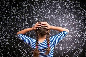 Thinking girl holding head against big blackboard, back view