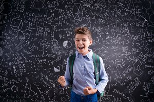 Excited and victorious boy against blackboard with mathematical