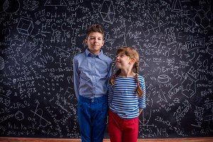 Happy boy and girl at school against big blackboard.