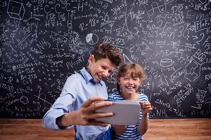 Boy and girl  with smartphone, taking selfie, against blackboard