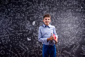 Boy with notebooks against big blackboard with mathematical symb