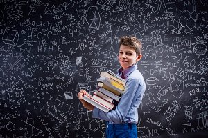 Boy with books against big blackboard with mathematical symbols