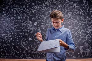 Boy holding notebook and chalk, big blackboard with formulas