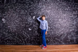 Boy against big blackboard with mathematical symbols and formula