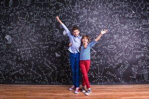 Cute little boy and girl in front of a big blackboard.
