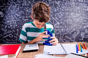 School boy at the desk with microscope, big blackboard