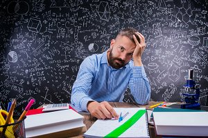 Upset teacher at desk, school supplies, holding head, blackboard