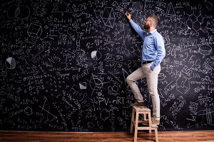 Man writing on big blackboard with mathematical symbols