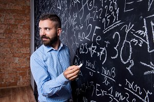 Hipster teacher writing on big blackboard with mathematical symb