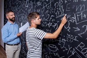 Teacher and student writing on big blackboard with mathematical