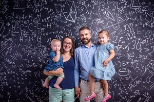 Young family with two little daughters against big blackboard