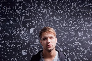 Student against a big blackboard with mathematical symbols