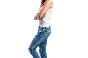 Standing teenage girl in jeans and white singlet,  isolated