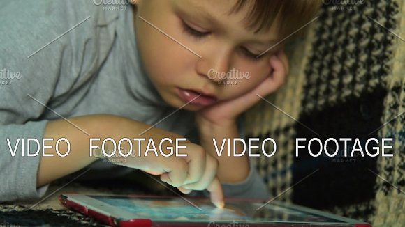 Kid Searching For Game On Digital Tablet