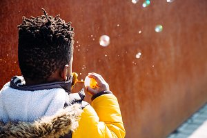 Kid blowing bubbles on the street