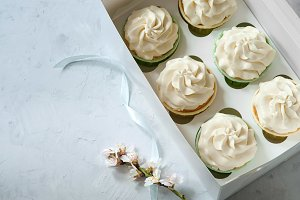 Present concept. Fresh white flowers and gift box with cupcakes on wooden table. place for inscription. Mother's Day, Lovers' Day, Birthday