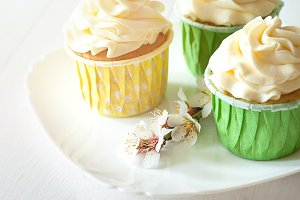 Three handmade cupcake dessert on a white plate with a sprig of spring flowers