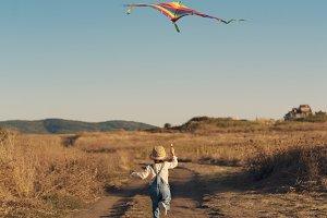 Little running girl with flying kite