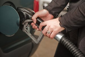 Woman's Hands Pumping Gasoline at th