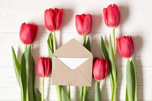Little envelope on red tulips