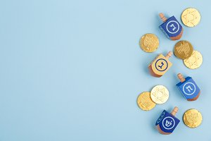 Dreidels & coins on blue background