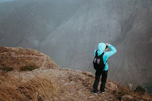 Man in high altitude rocky mountain landscape in front of a deep ravine. Trekking trail on Santo Antao Cape Verde