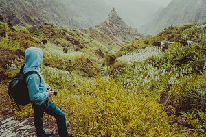 Traveler with backpack looking for motive of rural landscape with mountain peaks and ravine in dust air on the path from Xo-Xo Valley. Santo Antao Island, Cape Verde