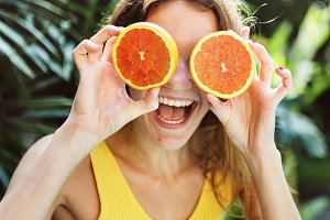 Happy young woman with oranges