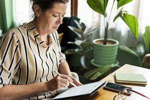 Woman writing to do list on tablet