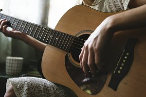 Woman relaxing and playing guitar