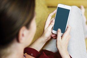 Woman using smartphone on sofa (PSD)