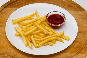 French fries with red sauce on a whi