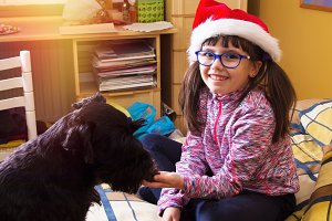 girl with santa hat and dog