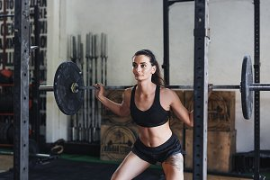 Young woman exercising with barbell