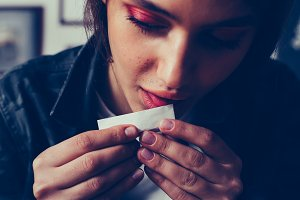 young woman licking cigarette paper