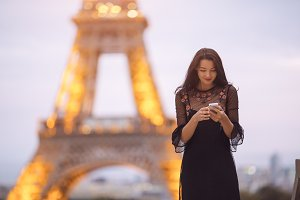 Travel woman using smartphone near the Eiffel tower and carousel, Paris. Evening little noisy image.