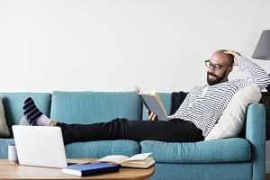 Bearded man reading on the couch