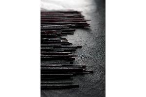 Black dry rice noodles on black stone partial blur