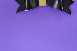 Black and golden bow tie over ultra violet background.