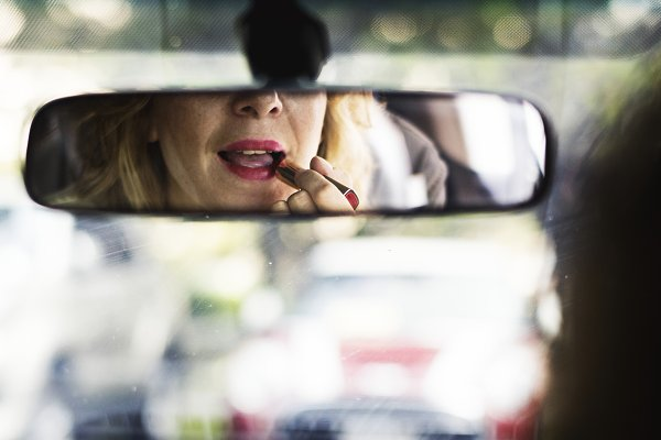 Woman putting on lipstick in a car