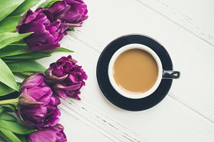 Cup of coffee with bouquet of ultraviolet tulips